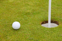 Golf ball on lip of cup Stock Images