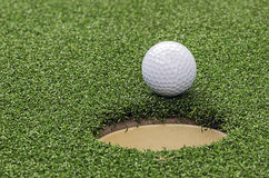 Golf  ball on lip of cup Royalty Free Stock Image