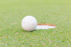 Golf ball on lip of cup Stock Photography