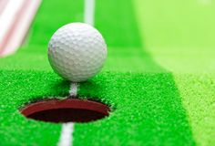 Golf ball on lip of cup, goal concept stock photo