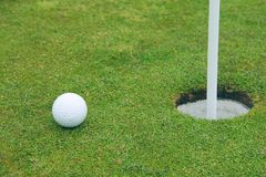 Golf ball on lip of cup Stock Photos