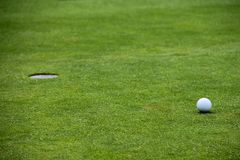 Golf ball on lip of cup Stock Image