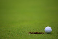 Golf ball on lip of cup Royalty Free Stock Photos