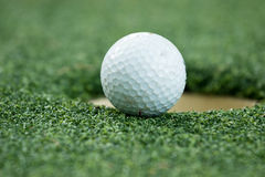 Golf ball on lip of cup Royalty Free Stock Photography