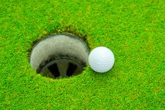 Golf ball on lip of cup, Golf ball and golf hole on green grass. royalty free stock photos
