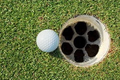 golf ball at lip hole Royalty Free Stock Image