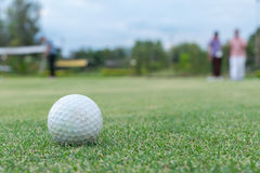 Golf ball lip of hole on green Royalty Free Stock Images