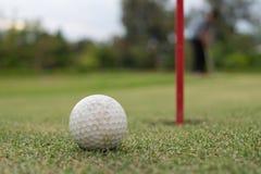 Golf ball lip of hole on green stock photos