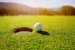 Golf ball on lip of hole over beautiful green loan Royalty Free Stock Photos