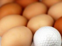 Golf ball lying among the eggs. Stock Photography