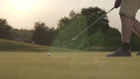 The golf ball lying on the grass in the sun rays. Unrecognized mature man moving the ball with a golf club. Summer. Leisure. Slow motion stock video