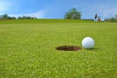 Golf, ball lying on the green next to hole Royalty Free Stock Image