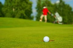 Golf, ball lying on the green next to hole, in the background goes golfer Stock Photos