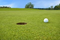 Golf, ball lying on the green next to hole Stock Photo