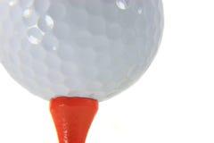 Golf Ball Macro. Macro of a golf ball on an orange tee isolated on white royalty free stock photo