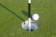 Golf Ball and Marker. A Black and White Marker indicates the Hole with Golf Ball Posed stock photos
