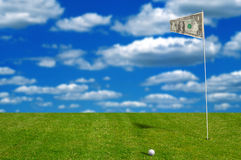 Golf ball with money flag. With sky in the background Royalty Free Stock Photography