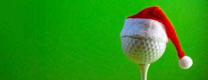 The golf ball mounted on the tee is wearing a Santa Claus souvenir hat. Blank for a postcard for a golfer to celebrate the New