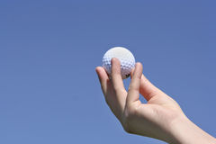 Golf ball in my hand with a bl Royalty Free Stock Images