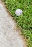 Golf ball near the cart path. Close up dirty golf ball on grass near the cart path Stock Photography