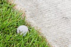 Golf ball near the cart path. Close up dirty golf ball on grass near the cart path Stock Photos