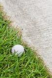 Golf ball near the cart path. Close up dirty golf ball on grass near the cart path Royalty Free Stock Photo