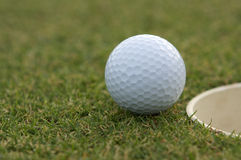 Golf Ball near the cup Royalty Free Stock Images
