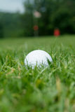 Golf-ball near the green. Golf-ball partly hidden just outside the green. Very shallow depth of field. Golf-ball in focus Stock Image