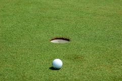 Golf ball near hole. White golf ball near hole. I was playing with DOF Stock Photography