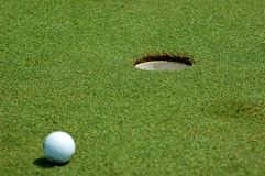 Golf ball near hole. White golf ball near hole. I was playing with DOF Stock Photo