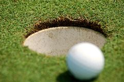 Golf ball near hole. White golf ball near hole. I was playing with DOF Royalty Free Stock Photos