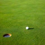 Golf ball near hole. Closeup of golf ball near hole on golf course green stock photography