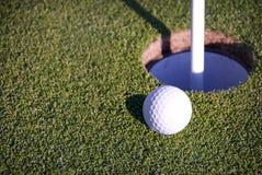 Golf Ball Near Hole Stock Images