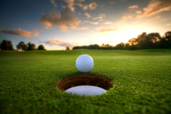 Golf Ball near hole. Golf ball about to fall into the cup at sunset Stock Images