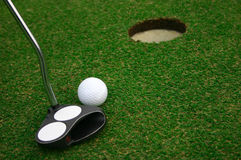 Golf Ball near Hole. Putter and golf ball ready to hit to the hole Stock Photography