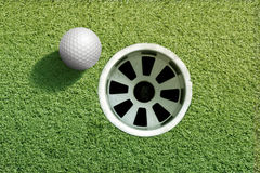 Golf ball near hole Royalty Free Stock Photography