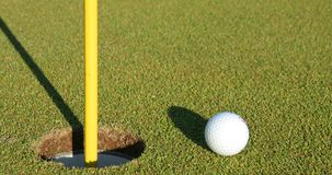 Golf ball near hole. Close up Stock Photography