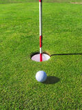 Golf ball near the hole. Royalty Free Stock Photo