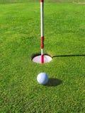 Golf ball near the hole. Royalty Free Stock Photo
