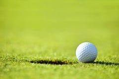 Golf ball near hole Royalty Free Stock Photos
