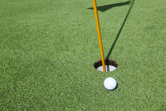 Golf ball near the hole Royalty Free Stock Photo