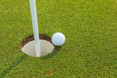 Golf ball near the hole. Close up golf ball near the hole in golf course Stock Images