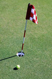 Golf ball near hole and flag. Elevated view of golf ball on green near hole and flag Stock Image