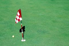 Golf ball near hole and flag. Golf ball on green near hole and flag with copy space Royalty Free Stock Photography