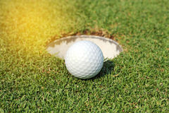 Golf ball near the hole Royalty Free Stock Image