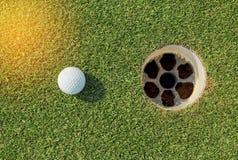 Golf ball near the hole Royalty Free Stock Image