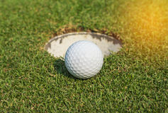 Golf ball near the hole Stock Image