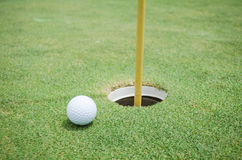 Golf ball near the hole Royalty Free Stock Images
