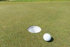 Golf ball near the hole Stock Photo