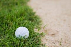 Golf ball near sand trap Royalty Free Stock Photos